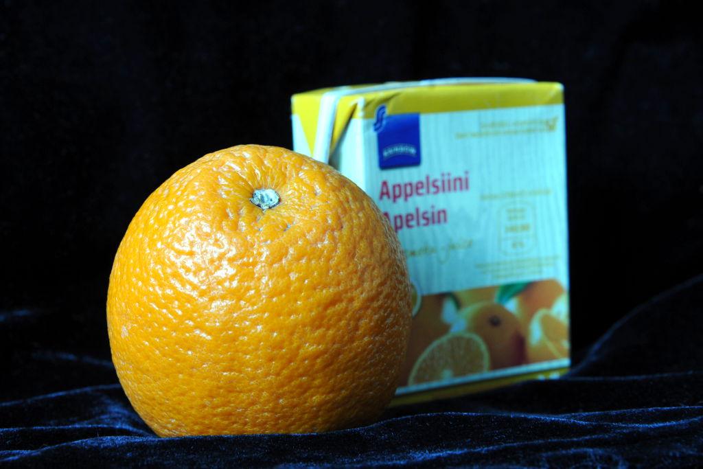 Appelsiini ja pieni purkki appelsiinimehua vierekkäin tummalla alustalla.